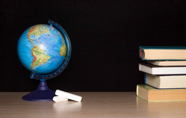 Model globe on the table, chalk and a stack of books on a dark background. school, training, the concept of obtaining knowledge
