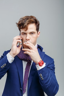 Model handsome guy in a suit with a cigarette and talking on the phone