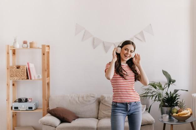 모델은 좋아하는 소파와 책장으로 둘러싸인 아늑한 아파트에서 시원한 시간을 보냅니다.