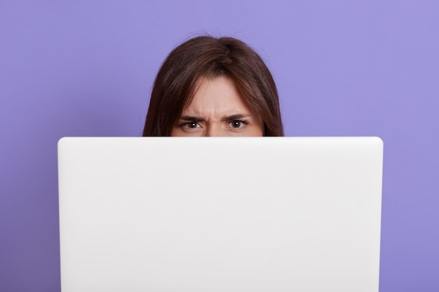 Model hiding behind laptop isolated over lilac wall, having angry facial expression, dark haired female behind white note book, freelancer during work.