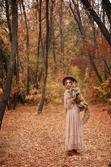 Модель держит лису в лесу