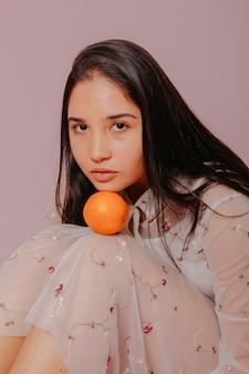Модель держит апельсин.