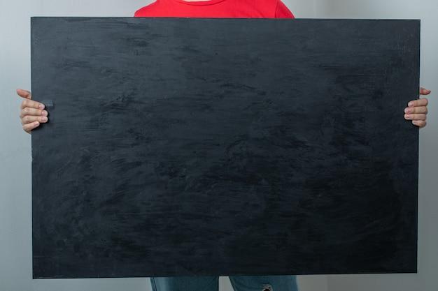 Model holding a black matte background.