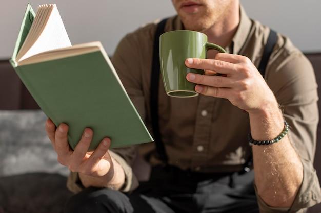 Модель держит чашку кофе и читает