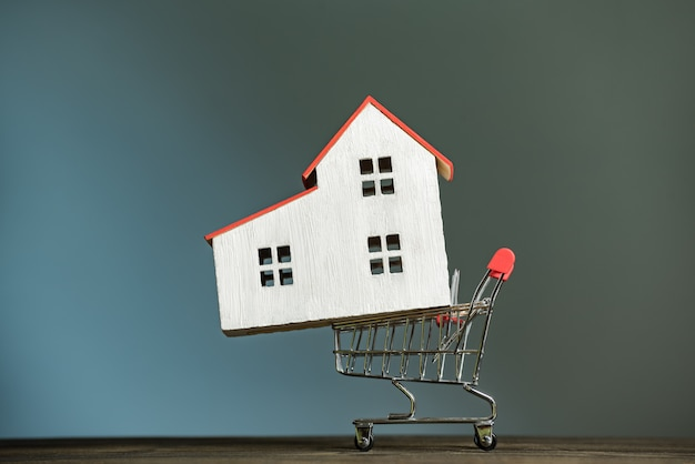Model home on the shopping cart. buy house concept. dark background, front view.