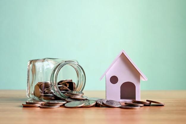 모형 주택 및 돈을 절약하는 병 부동산 투자 아이디어에서 동전 더미