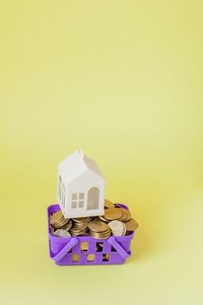 Модельный дом и монета в концепции корзины для покупок для экономии ипотечного кредита на желтом