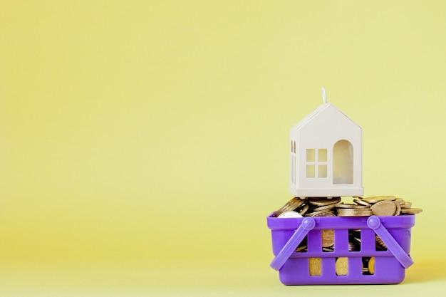 Модель дома и монета в корзине для покупок