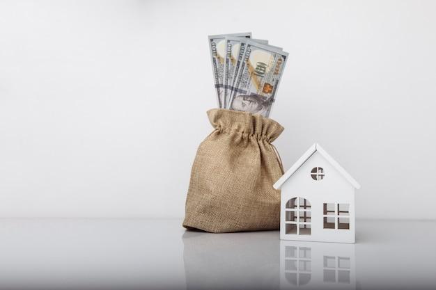 달러 지폐와 모델 하우스와 돈 가방입니다.
