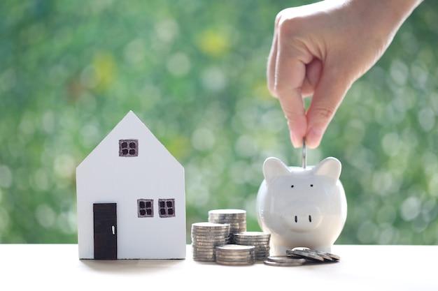 自然の緑の背景にコインのお金のスタックを持つモデルの家と貯金箱、将来の準備と不動産の概念のためにお金を節約する