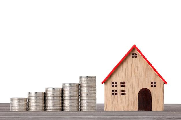 Модельный дом и укладка монет экономят рост на деревянном столе на белом студии для финансовой недвижимости