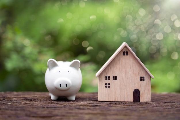 自然の背景の建設と不動産購入の計画に関するモデルハウスと白い貯金箱