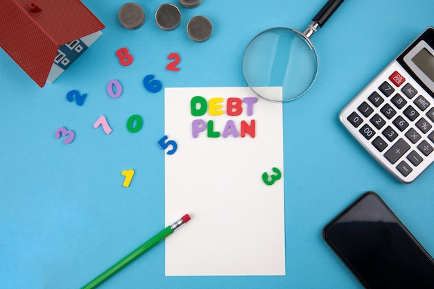 Model house, calculator, coins, magnifying glass with the word debt plan