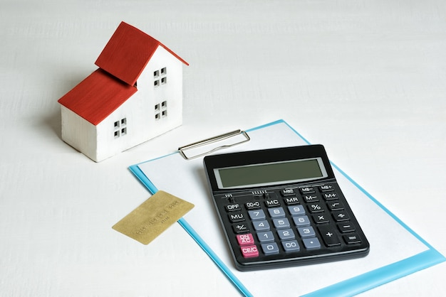 Model of house, credit card and calculator on. buying a home. concept of mortgage and real estate.