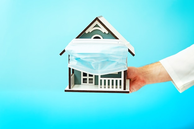 Model house in the hands of a doctor on blue background, house with protective medical mask. safety to stay at home