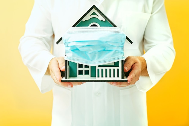 Model house in the hands of a doctor, house with protective medical mask. safety to stay at home