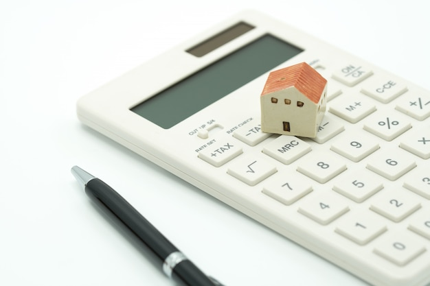 A model house model is placed on a calculator. as background property