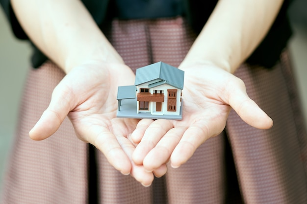 A model house model is placed on the hands of asian business girl