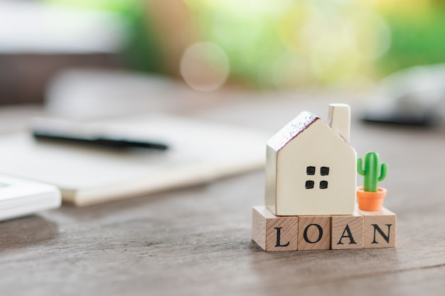 A model house model is placed on a notebook wood word loan