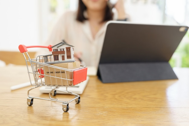 A model house model is placed on a shopping cart in the mall.