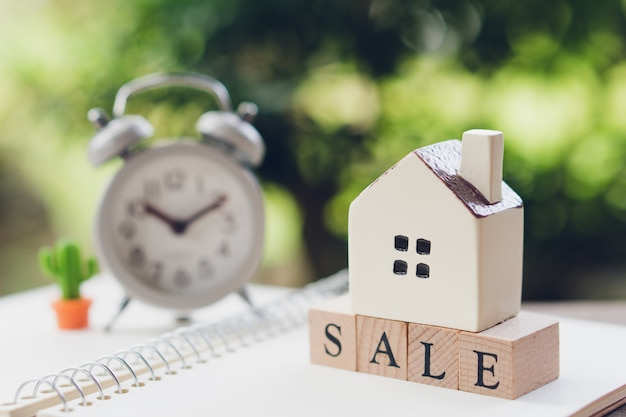 A model house model is placed on wood word sale . as background property