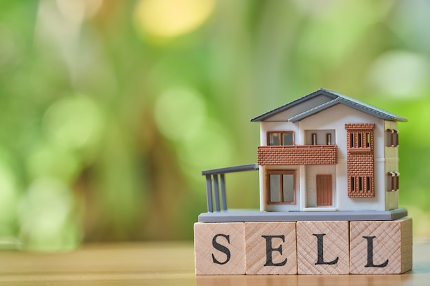A model house model is placed on wood word sell