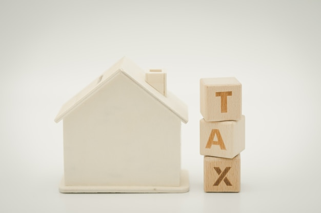 A model house model is placed on wood word tax . as background property real estate