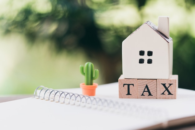 A model house model is placed on wood word tax . as background property