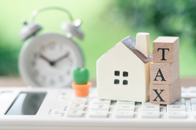 A model house model is placed on wood word tax .