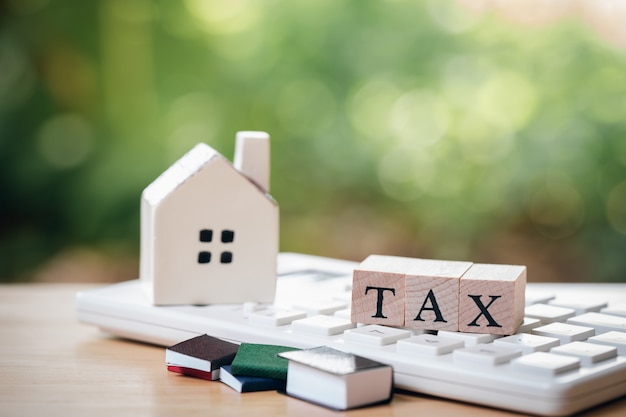 A model house model is placed on wood word tax