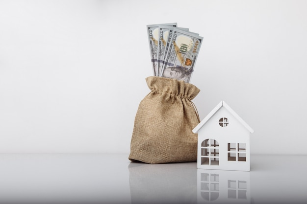 Model house and money bag with dollar banknotes.