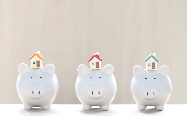 Model house and piggy bank on white background,business investment and real estate concept