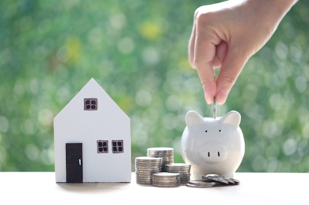 Model house and piggy bank with stack of coins money on nature green background,save money for prepare in future and real estate concept