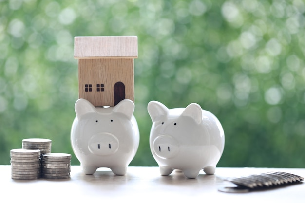 Model house on piggy bank with stack of coins money on nature green background
