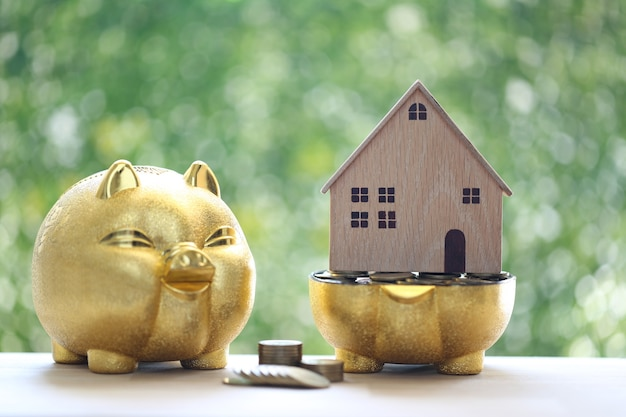Model house and stack of coins money in piggy bank on natural green background