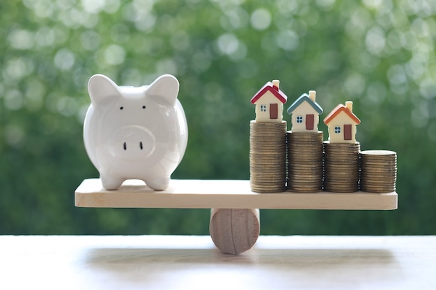 Model house on stack of coins money with piggy bank on wood scale seesaw with natural green background