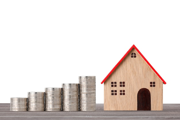 Model house and stacking coins saving growth on wooden desk on white studio for financial real estate