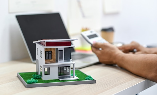 Model house on a table with blurry a person background using calculator and a laptop on the table, real estate expenses.
