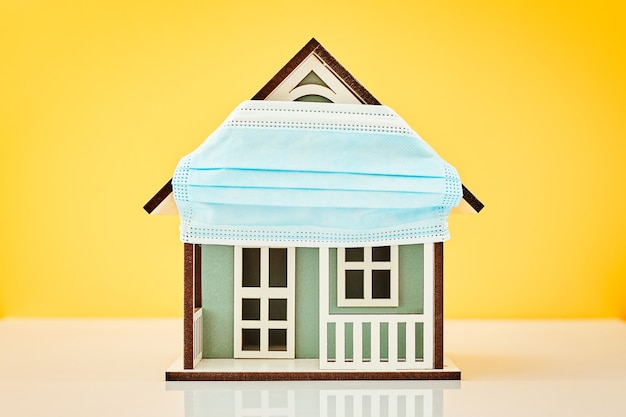 Model house wearing protective medical mask in yellow background
