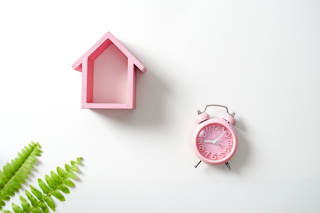 Model house with a clock on a white background finance insurance themed concept flat lay