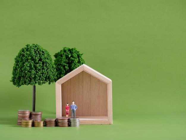Модельный дом с миниатюрными людьми и монетами на зеленом фоне. место для текста