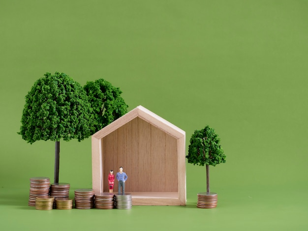 緑の背景にミニチュアの人々とコインのモデルハウス。テキスト用のスペース