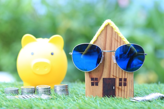 Модель дома с солнцезащитными очками и стопкой монет на натуральном зеленом