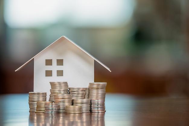 Модели домов и сложенные монеты. ссуды под залог недвижимости. ипотека и кредиты.