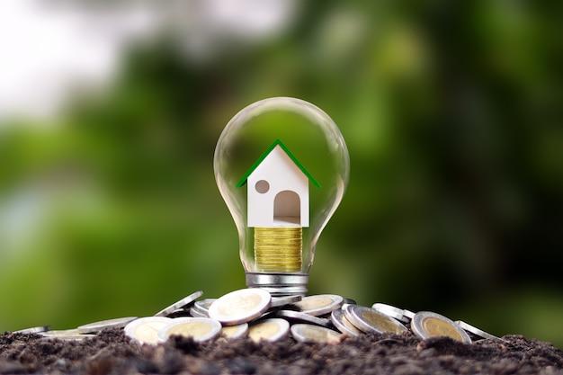 Модельные дома лежат на стопках монет в энергосберегающих лампах. концепция энергосбережения. возобновляемые источники энергии и инвестиционные ссуды.