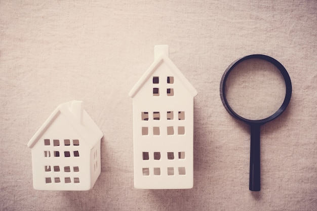 Model houses and magnifying glass, house searching