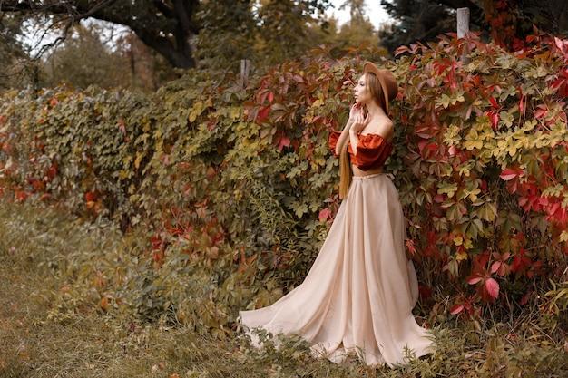 秋の背景に美しい秋のドレスを着たモデル。テキスト用の空き領域。