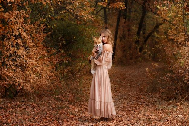 Модель в платье с рыжей лисицей в осеннем лесу