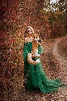 Модель в зеленом платье с рыжей лисицей в осеннем лесу