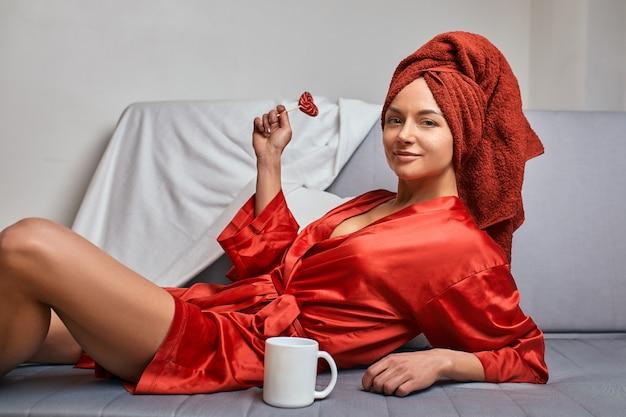 赤いマグカップとロリポップが付いたソファーに赤いバスローブと赤いタオルのモデル。ファッション、色のゲーム、ミニマリズムの概念。仕事から休み、休憩。